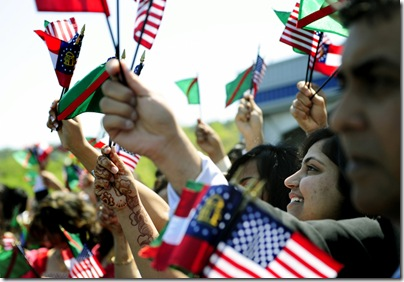 Sannah Vasaya, 18, from Snellville waves flags with other members of the Ismaili community.