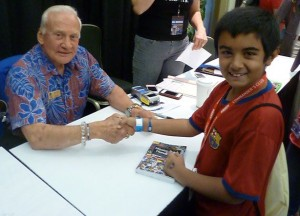 Qayl Maherali shakes hands with Astronaut Buzz Aldrin at Kennedy Space Center.