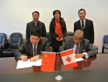 Chair of the BCIT Board of Governors, Taj Mitha (seated, right), signs a MOU as Dean of BCIT International Lawrence Gu (standing, right) and members of the Chinese delegation look on.