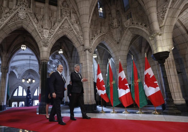 Canada's PM Harper walks with the Aga Khan in the Rotunda on Parliament Hill in Ottawa