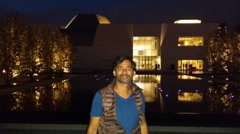 Imran Qureshi takes a break to pose for a picture with the Aga Khan Museum in the background. (Image: Ismailimail/AM)