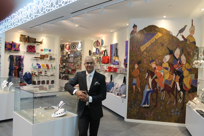AKM Gift Shop - Shoheb Gwaduri, Aga Khan Museum's Manager of Business Development standing at the entrance of the Gift Shop with products from 15 different countries.