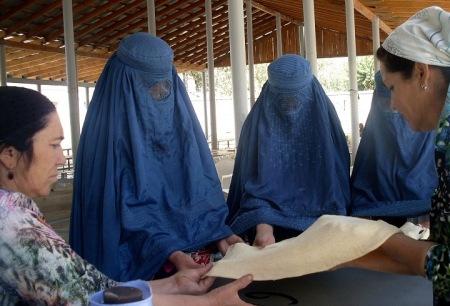 Tajik women teach veiled Afghan women how to bake traditional bread in a tandoor oven in Darvoz, Tajikistan, in June. [Central Asia Online/Nadin Bahrom]