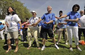 B.C. Premier Gordon Campbell (left) warms up with the crowd on Sunday, before the beginning of the 25th annual World Partnership Walk in Stanley Park. Photograph by Ward Perrin, Vancouver Sun 2009