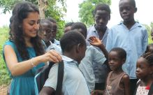Salima Visram helps a student try out her Soular Backpack (Image via Forbes)