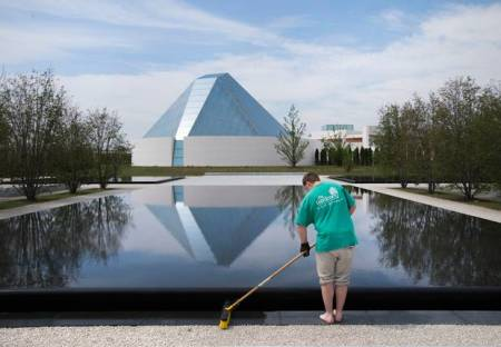 The Ismaili Centre is reflected in a pool as a landscaper works in Aga Khan Park in Toronto. (Darren Calabrese for The Globe and Mail)