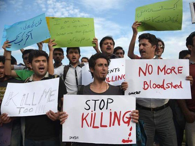 Pakistani civil society activists carry placards as they shout slogans during a protest against the killing of the Shiite Ismaili minority. (PHOTO: AFP via The Express Tribune)