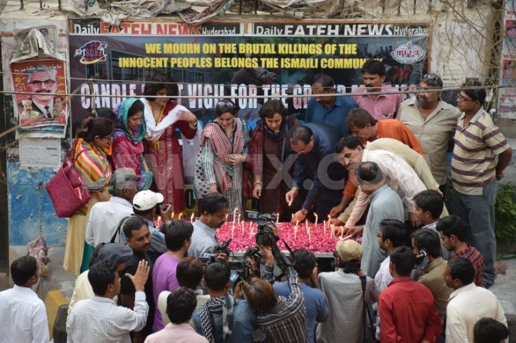 Members of Hyderabad union of journalist light candles during vigil for the 48 people killed in a bus attack in Karachi's Ismaili community. (Image via Demotix)