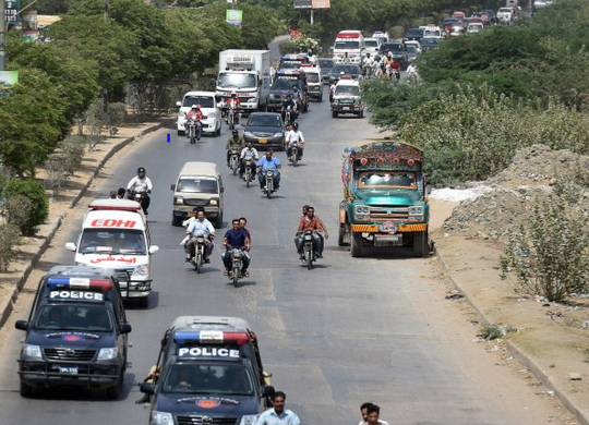 May 13, 2015 Pakistani security personnel escort ambulances carrying the bodies of Ismaili Muslims following the attack in Karachi. (Image credit: Asif Hassan/AFP/Getty Images via The Washington Post)