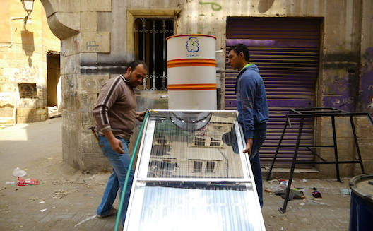 Ahmed Mahmoud and Mohamed Moustafa work on Shamsina's solar water heater in Cairo's Al Darb Al Ahmar slum. (Image; Rachel Williamson via Wamba)