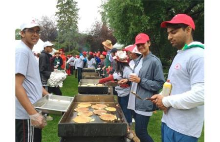 Hanif Kanji, right, prepares pancakes at the Ismaili Muslim community's Canada Day pancake breakfast at the legislature Wednesday.