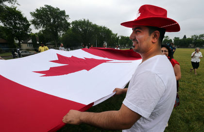 Jihad Ahmed help carry a giant Canadian flag at the 18th annual NorQuest College Canada Day celebrations in Edmonton, Alberta Tuesday, June 30, 2015. Perry Mah/Edmonton Sun/Postmedia Network