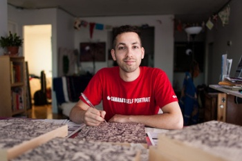 Aquil Virani works on one of the birch wood panels used to create Canada's Self Portrait. / Photo: Alex Tran