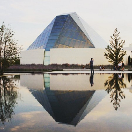The serene looking Ismaili Centre, Toronto reflected in one of the 5 infinity pools between the Centre and the Aga Khan Museum, all embedded within the unifying Aga Khan Park. The combined spaces of the Aga Khan Museum and the Ismaili Centre, Toronto within the Aga Khan Park are dubbed as the Aga Khan Cultural Hub. (Image via Blog TO)