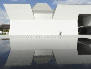 The Aga Khan Museum is reflected in pool.
