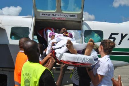 Medical personnel from AMREF Flying Doctors in Malindi carry Doris Mwangala onto a plane for Aga Khan University Hospital, Nairobi on Tuesday to undergo surgery to remove a brain tumour. (Image via The Star)