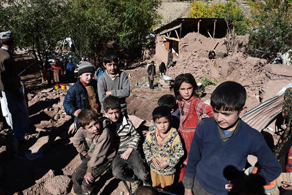 Pakistani earthquake survivor children gather in the midst of the rubble of destroyed homes in Charun Avir village, some 65 kilometers north of Chitral on October 29, 2015. Rescuers say they believe they have reached most of those affected by the powerful earthquake that ripped across Pakistan this week, but thousands of desperate survivors now face a race to rebuild with winter fast approaching. AFP PHOTO / Farooq NAEEM
