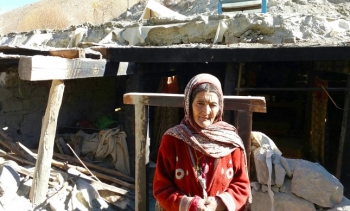A woman in Phandar, Ghizer stands before the remnants of her home, which collapsed in the 26 October earthquake. FOCUS
