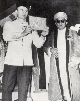 Prince Aly Khan displays the Platinum plaque which he received on behalf of his father on the occasion of his Platinum Jubilee celebrations in Bombay. Photo: Ilm, Centenary Issue, November 1977