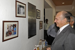 Mawlana Hazar Imam smiles as he looks at photographs of his visit to the Diamond Jubilee High School in 1958, and Princess Zahra's inauguration of the new site of the school in 2007. Photo: The Ismaili/Gary Otte