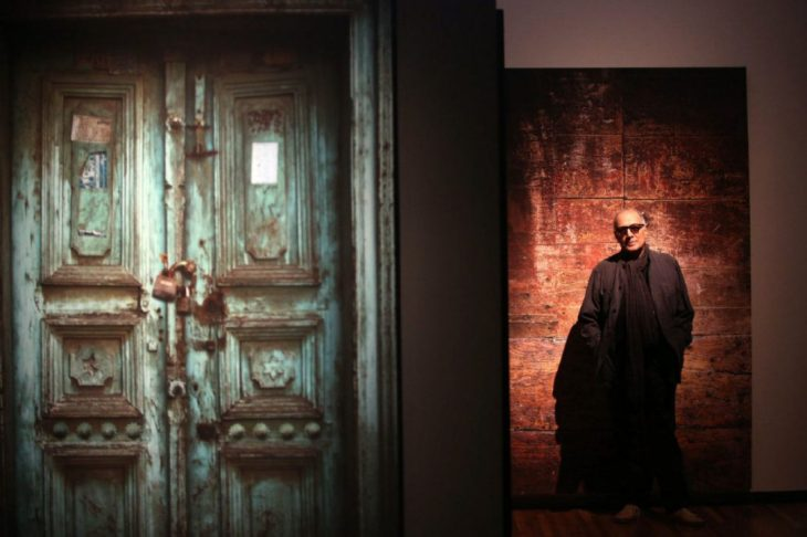 """Abbas Kiarostami in his installation """"Doors Without Keys"""" at the Aga Khan Museum. Kiarostami's exhibition features life-size photos of ancient doors. (Image credit: Vince Talotta via Toronto Star)"""