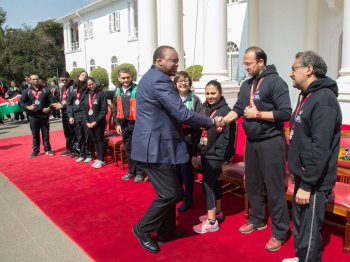 President of Kenya, Uhuru Kenyatta celebrates with medal winning Jubilee Games Team Kenya