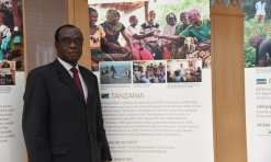 Tanzanian Ambassador Jack Mugendi Zoka stands next to a banner describing the work of the AKDN in his country. (Image credit: AKDN / Safiq Devji)