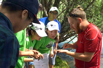 In the environmental monitoring workshop, bio-indicator expert Amadeus DeKastle identifies local organisms indicating the health of the Chong Ak Su river ecosystem.