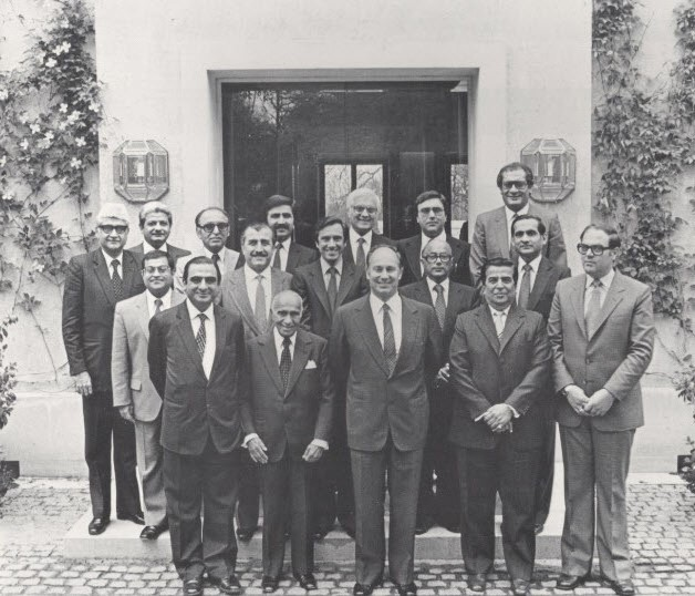 Mawlana Hazar Imam with Ismaili leaders at Aiglemont, 1982. First row, L to R:Vazir Badruddin Morani (India), Count Sir Eboo Pirbhai (Africa), Mawlana Hazar imam, Vazir Ramzan Merchant (Pakistan), Mr Tamer Tamer (Syria). Standing behind from L to R: Vazir Ameerali Rahimtoola (India), Mr. Shams Bhaloo (USA), Vazir Abdulmohamed Furniturewala (India), Vazir Mohammad Bhai (Bangladesh), General Moustapha Sharba (Syria), Mr Salim Issa (Portugal), Aitmadi Akbar Karmali (Pakistan), Mr Zulfikar Lalji (Canada), Mr Zulfikar Jiwa (Europe), Mr Jafferali Tejpar (Tanzania), Mr Kurban Bhaloo (Kenya), Rai Amir Bhatia (UK). Photo: 25 Years in Pictures