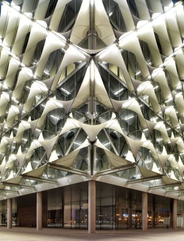 The square shaped new building is covered by a filigree sun protection textile façade following traditional islamic architectural patterns and linking them with state of the art technology. AKAA / Cemal Emden