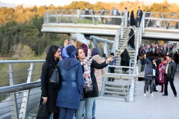 Iranian teenage girls posing. Aga Khan Award for Architecture 2016 Winner: Tabiat Pedestrian Bridge, Tehran