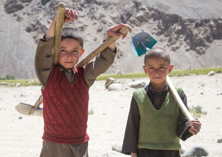 Two boys pose with shovels in the remote Afghan villages. (Image credit: Exclusivepix Media)