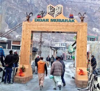 People walk through the special gate of Didargah in Aliabad, Hunza, on Sunday. — Dawn