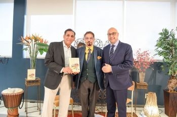 """Iqbal Dewji of Khojawiki.org, holding """"Diasporic Distractions"""", announces the official launchof the book as Mohamed Keshavjee and Ali Velshi look on."""