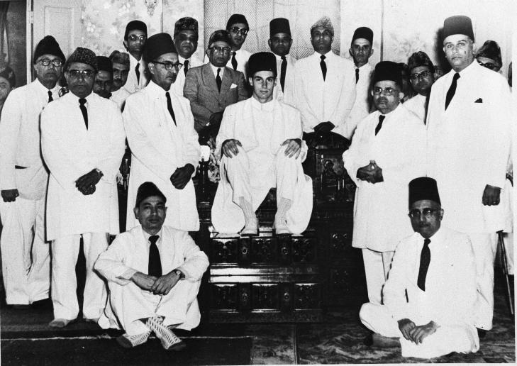 The new Aga Khan, seated at center, and former Prince Karim, grandson of the late Aga Khan, sits among his followers of the Ismaili Muslims in Bombay, India, Aug. 20, 1957. (AP Photo)